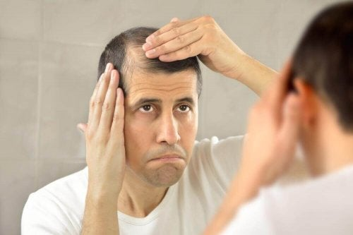 Mand tjekker sit hår i spejlet
