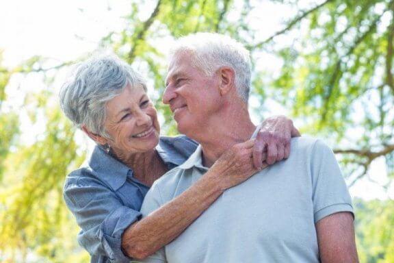 Ældre, smilende par, der krammer