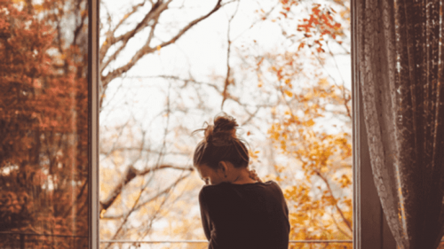 Kvinde i vindue foran efterårstræer