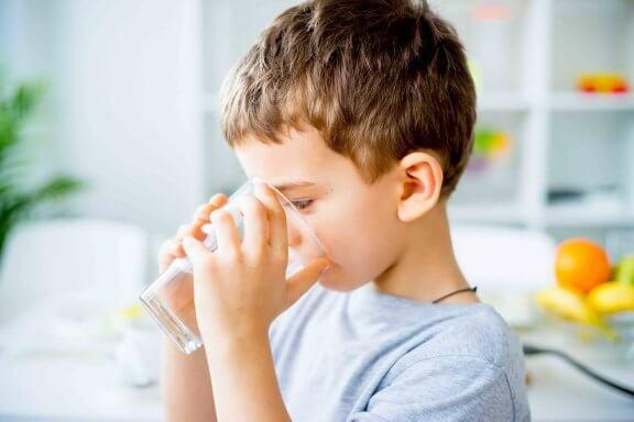 dreng drikker et glas vand for at bekæmpe forstoppelse hos børn