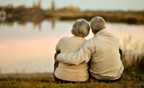 ældre par krammer hinanden og ser ud over sø