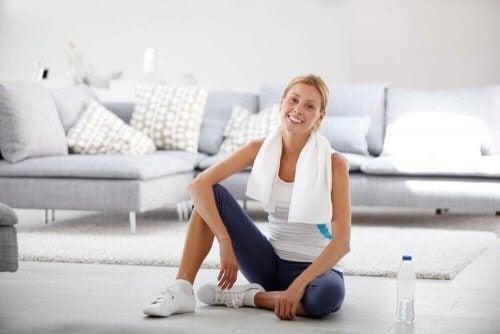 kvinde dyrker sport i stuen