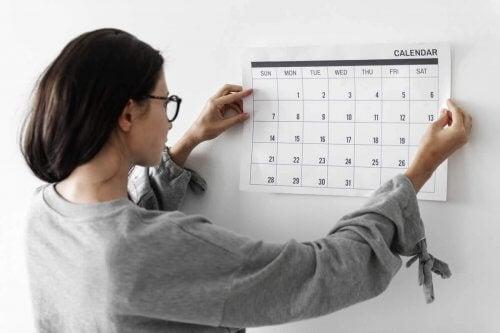 En kvinde sætter en kalender på væggen.