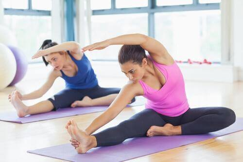En kvinde strækker sig for at forbedre fleksibiliteten i benene