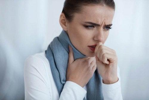kvinde tager sig til halsen