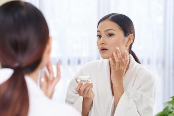 kvinde i gang med at smøre ansigtet med fugtighedscreme