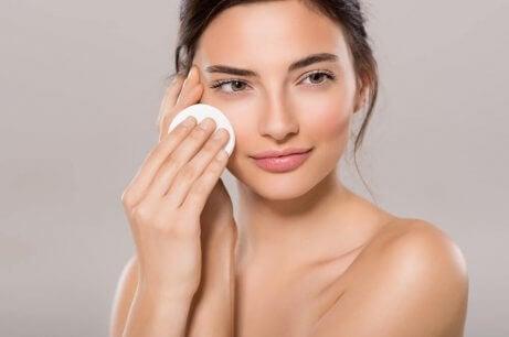 Kvinde anvender toner for at mindske porer