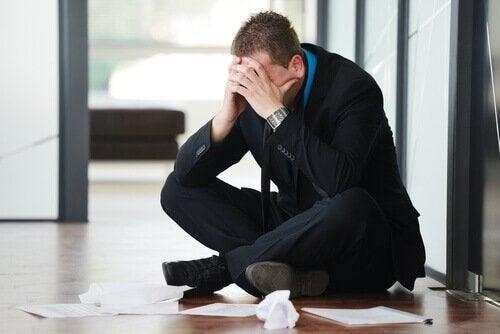 Mand på gulv på kontor er plaget af at arbejde for meget