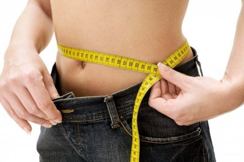 Kvinde måler mave for at tjekke for vægtforøgelse med alderen