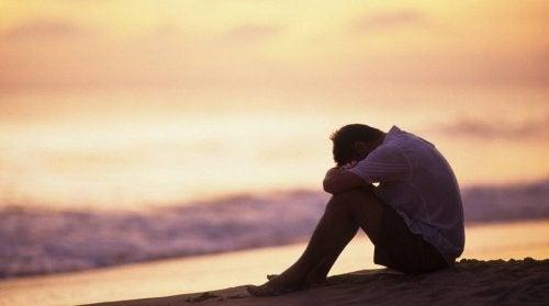 Mand på strand er deprimeret og hviler hoved på knæ