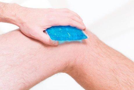 En mand har en ispose på knæet