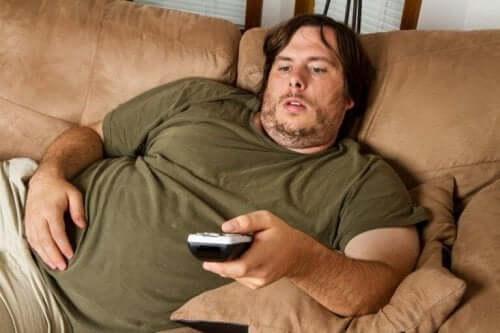 Mand ligger på sofa med fjernbetjening