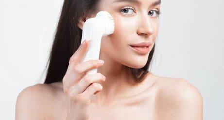 kvinde skrubber sit ansigt med en børste