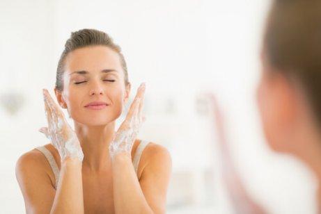 Kvinde foran spejlet vasker ansigt