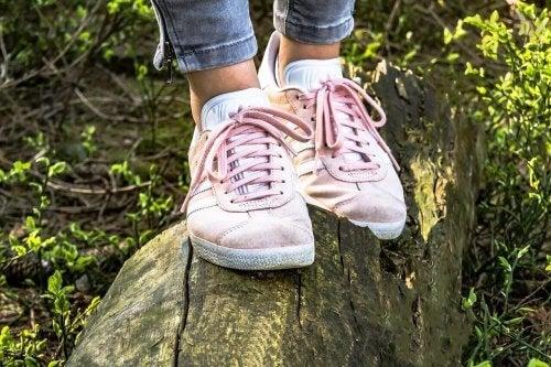 Person i sko på træstamme