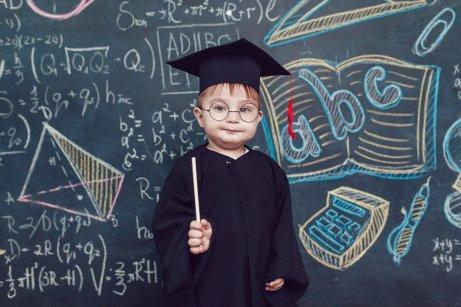 Et barn med en sort akademisk dragt
