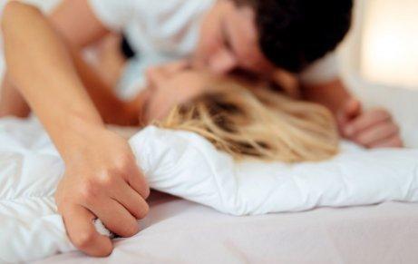Mand og kvinde kysser og prøver at undgå fejl i sengen