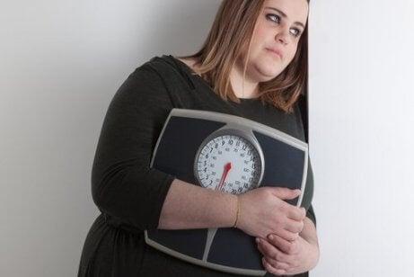 Overvægtig kvinde med vægt er klar til yoga til vægttab