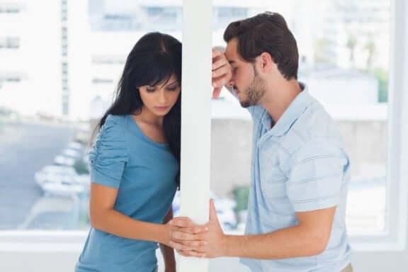 Mand og kvinde på hver side af væg holder i hånd, hvilket illustrerer, at en eks vil være venner