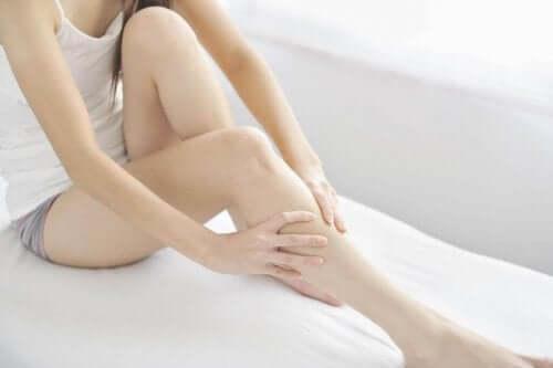 En kvinde masserer hævede ben