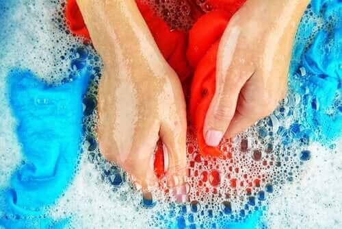 En kvinde vasker tøj med hænderne