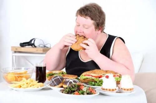 En mand spiser junkfood og illustrerer forskellene mellem sult og angst