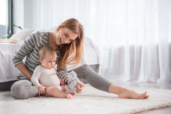 Moderen er i gang med at lære baby at sidde
