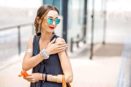 Kvinde smører solcreme på huden for at undgå solpletter