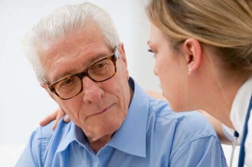 Kvinde prøver at hjælpe et ældre menneske med en sygdom