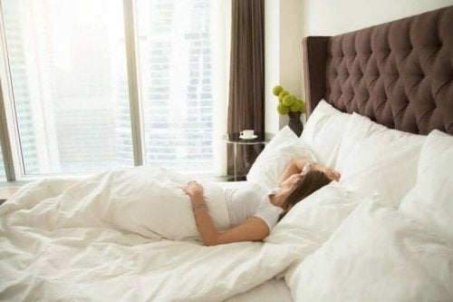 Kvinde ligger i behagelig seng