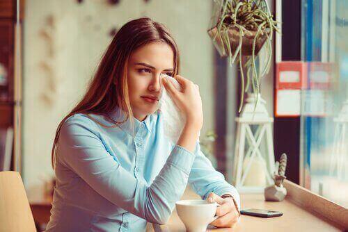 Kvinde græder og tørrer sine øjne