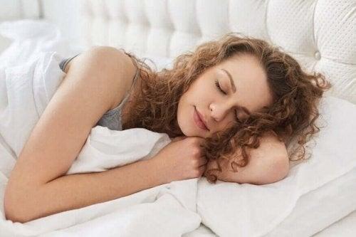Kvinde ligger og sover i sin seng