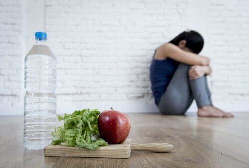 Trist kvinde nægter at spise salat og drikke vand