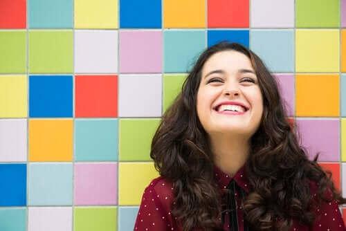 En smilende kvinde foran farverig væg