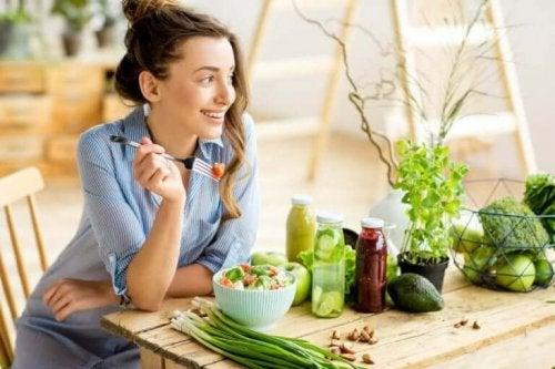 Silende kvinde i køkken fyldt med grøntsager
