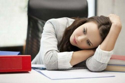 Træt kvinde på arbejde hviler sig på bord