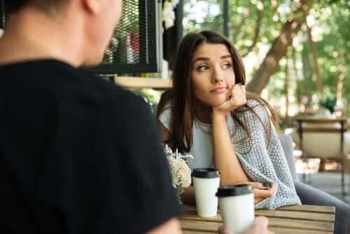 Kvinde kigger væk, mens mand taler til hende