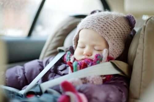 En baby, der er ved at sove i en autostol