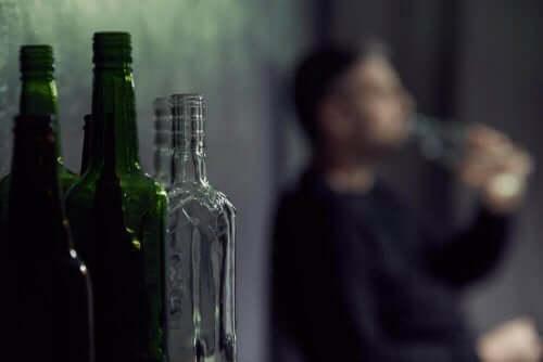 Mand med alkoholproblem ses sløret bag tomme flasker
