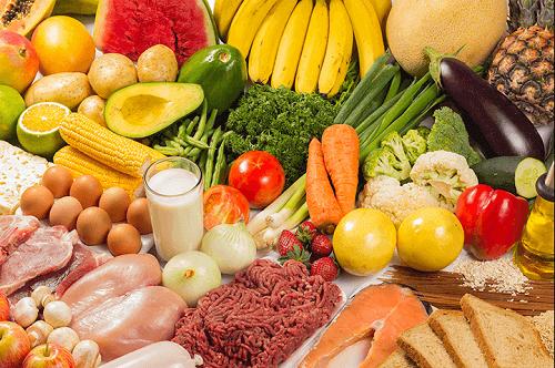 Et bord fyldt med frugt, grønt og andre sunde fødevarer