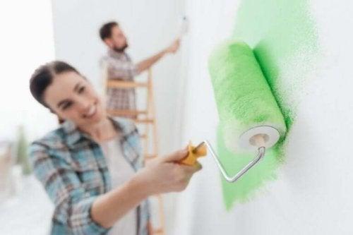 Lykkelige par udfører husligt arbejde sammen, som dette par, der maler