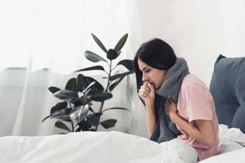 Kvinde i seng oplever feber og kropssmerter, som er en af de største forskelle mellem forkølelse og influenza