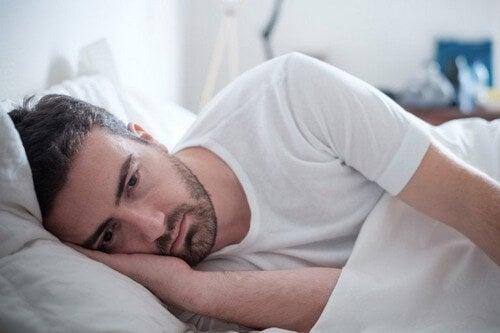 Mand ligger i sin seng og er trist