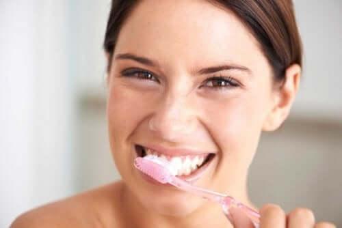 Kvinde børster tænder med produkter til at blege tænder