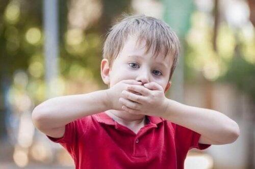 Dreng holder sig for munden