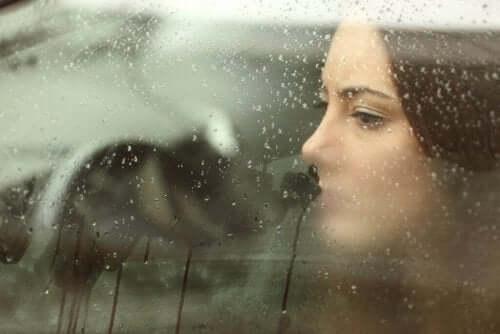 Kvinde i bil ser ud af vindue med regn på