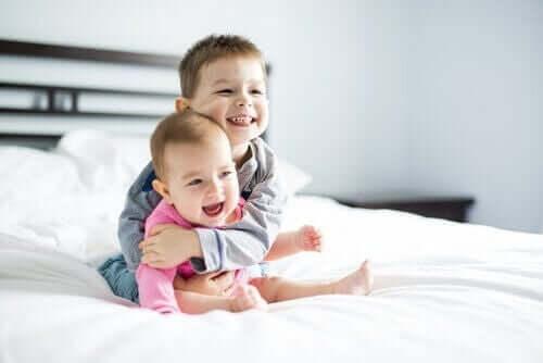 Søskende krammer i seng
