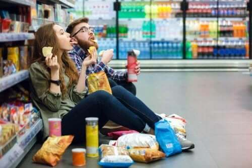 Mand og kvinde sidder i gang i supermarket og spiser chips