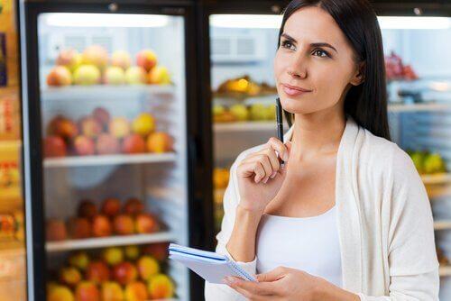 Kvinde ved køleskabe fyldt med frugt