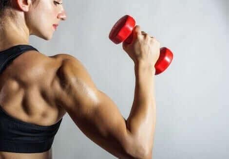 Kvinde med håndvægt forsøger at undgå biceps tendinitis